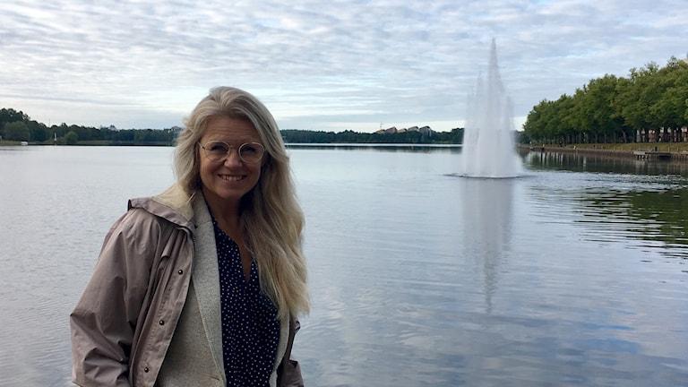 En kvinna står vid Växjösjön. Bakom syns en fontän som sprutar vatten.