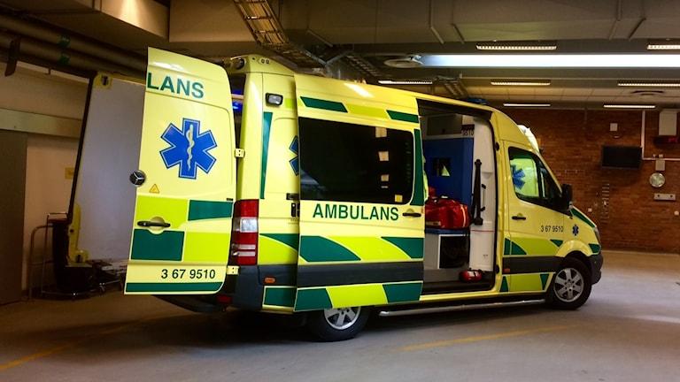 En parkerad ambulans med öppna dörrar i ett garage