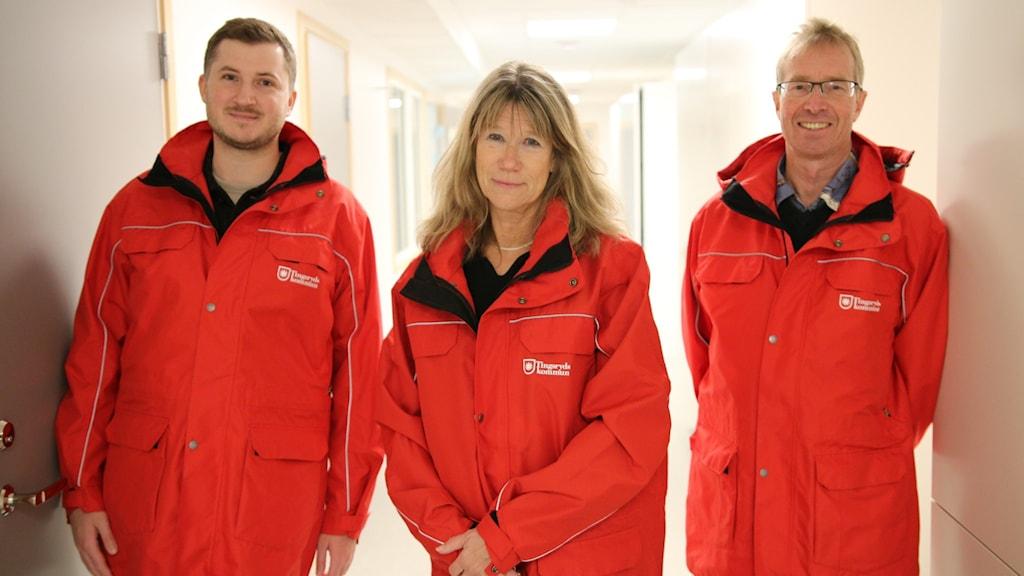 Magnus Carlberg, Anette Weidenmark och Mikael Jeansson visar upp de röda jackorna som köps in till anställda i kommunen.