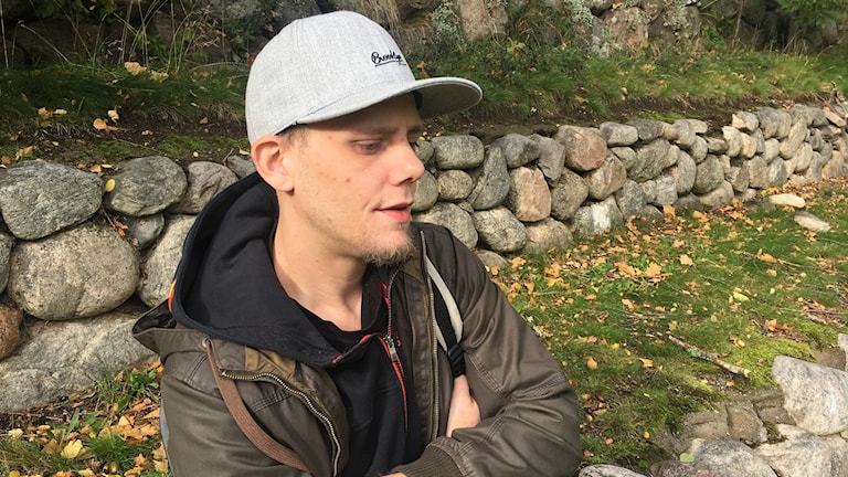 I bild Mikael som har en grå keps, brun jacka, lutar mot en stenvägg. Han tittar ner i marken.