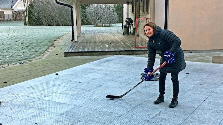Riika Välilä spelar hockey i trädgården.