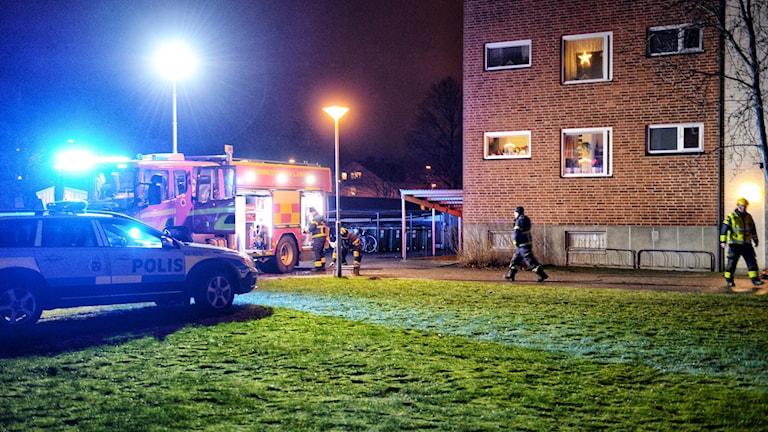 Polisbil och brandbil framför lägenhetshus.