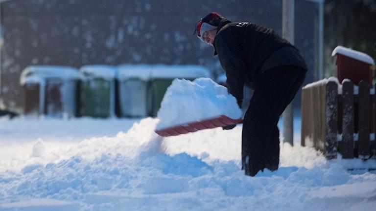 Man som skottar snö