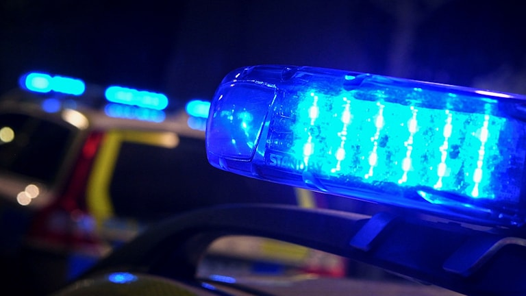 Polis på plats med blåljus på taket.