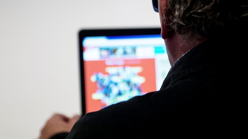 Nacken och axeln bakifrån av en man som sitter vi en dator. Genrebild.