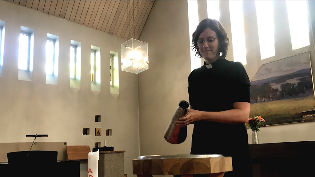 En kvinnlig präst vid en dopfunt