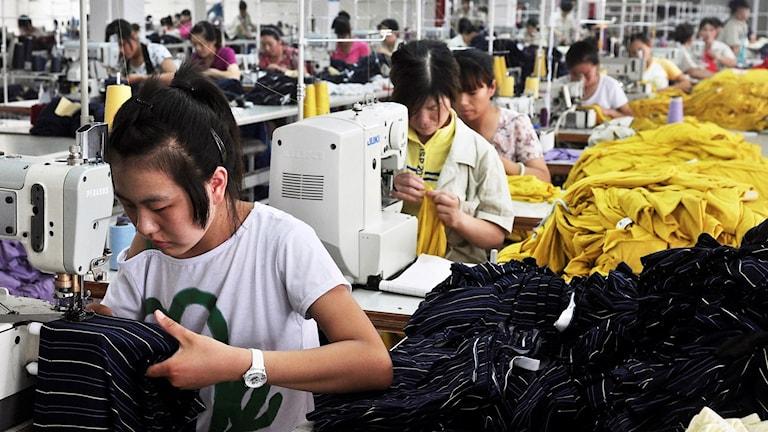 Kvinnliga kinesiska fabriksarbetare sitter vid symaskiner och syr kläder.