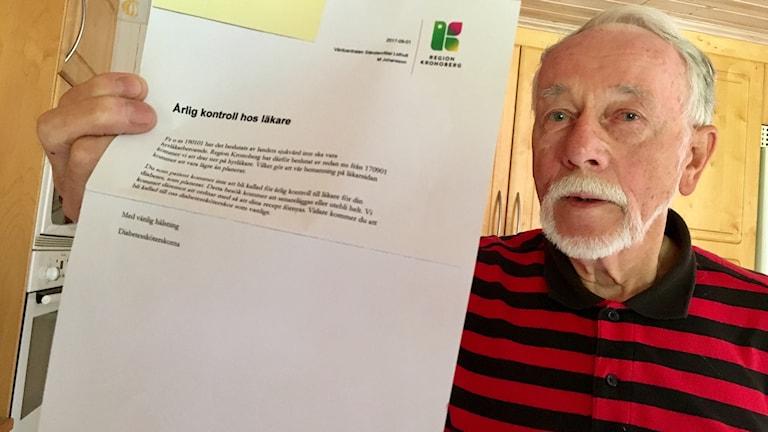 Olle Petersson visar upp brevet från Region Kronoberg.