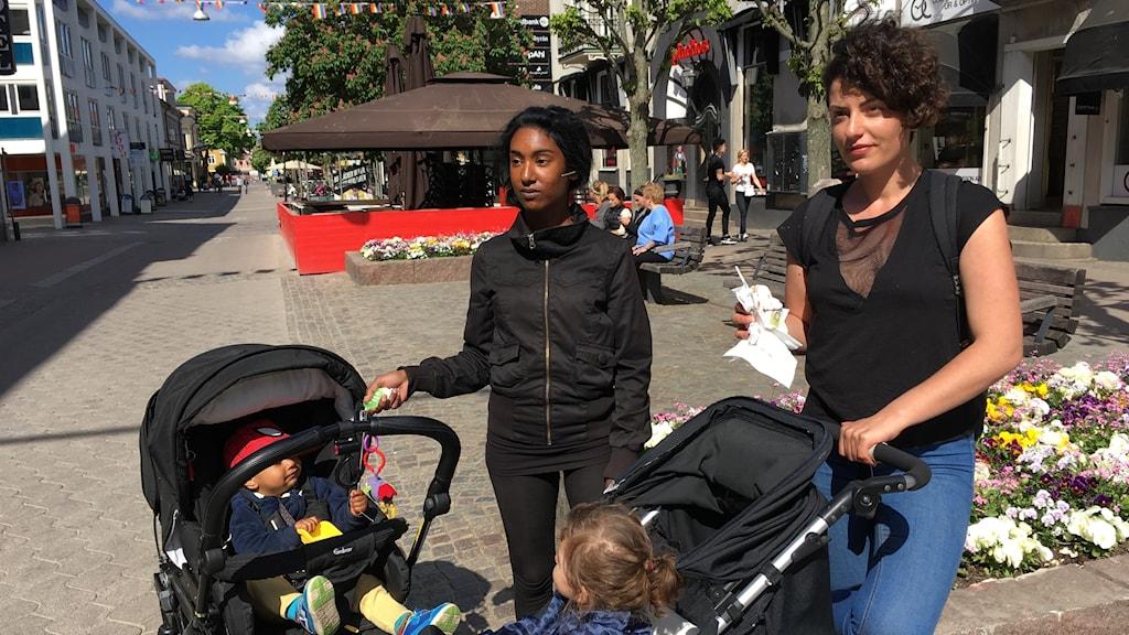 Två kvinnor står med barnvagnar på en gata
