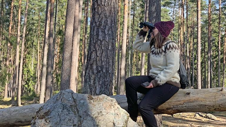 En kvinna sitter på en stock och spejar genom sin kikare.