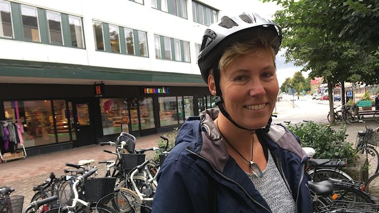 En kvinna med cykelhjälm på sig står vid ett gäng parkerade cyklar på en gågata