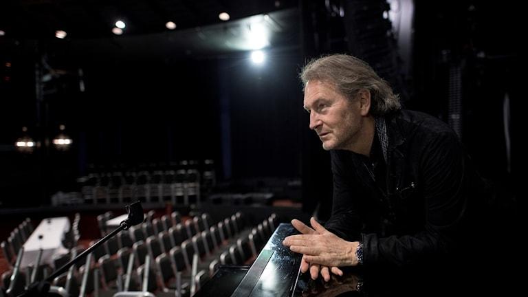 Tomas Ledin står i svarta kläder och blickar ut mot arenan.