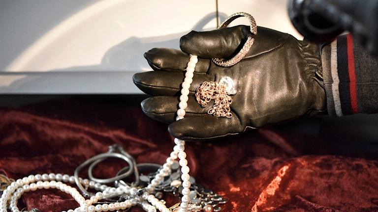 En hand som stjäl pärlhalsband och andra smycken. Arrangerad.