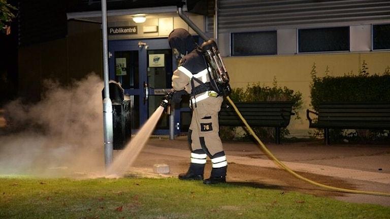 Räddningstjänsten släcker eld i papperskorg.