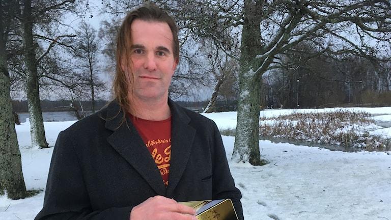 En man står utomhus i ett vinterlandskap. En sjö är i bakgrunden.
