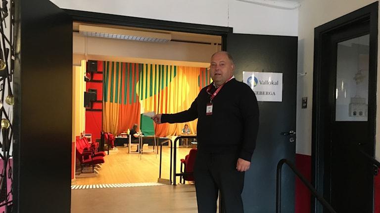 En man står vid dörröppningen till en vallokal