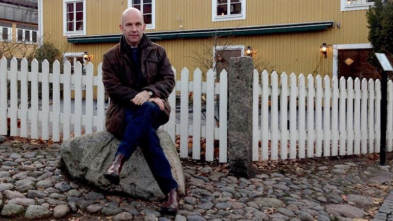 Fredrik Modéus, biskop i Växjö stift sitter på en sten framför ett gult hus och ett vitt staket.