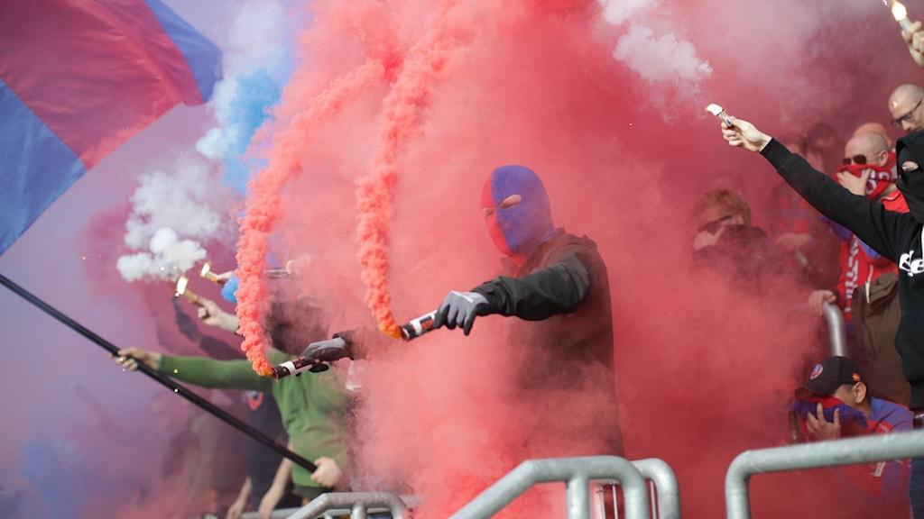 Personer med bengaler på en fotbollsläktare.