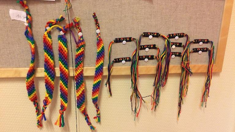 Flera armband i regnbågens färger uppnålade på en anslagstavla.