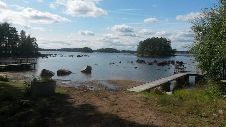 En strand vid sjön Rottnen där tre större stenar sticker upp från vattenytan. Där ska den nu bortgrävda ön tidigare ha legat. Foto: Länsstyrelsen