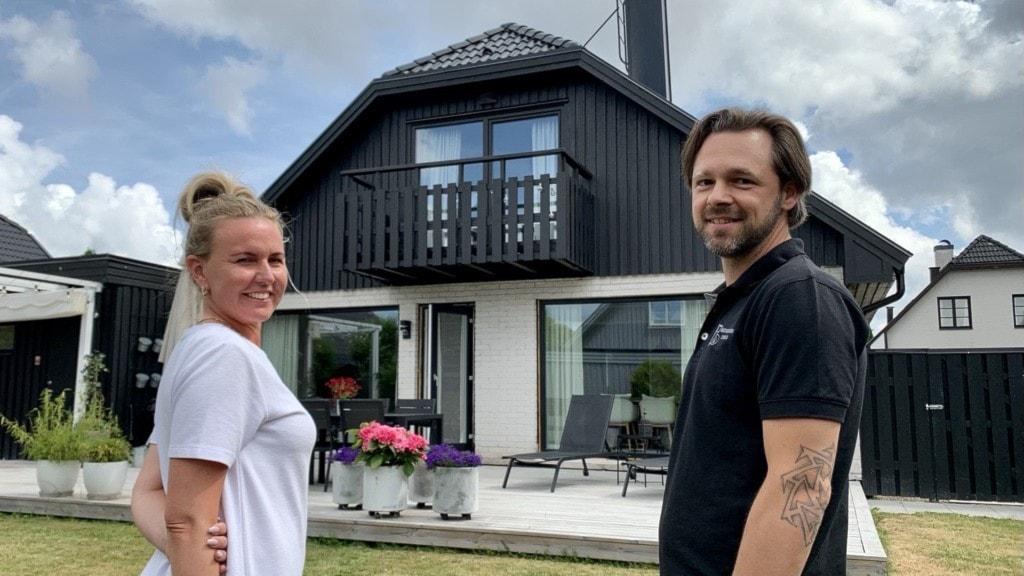 Två personer vid ett stort svartvitt hus.