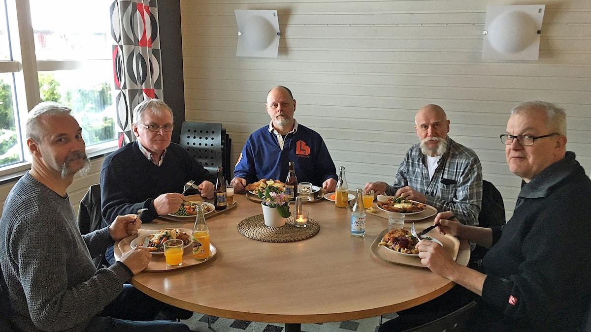 Fem män sitter och äter i lunchrummet på Cargotec i Lidhult