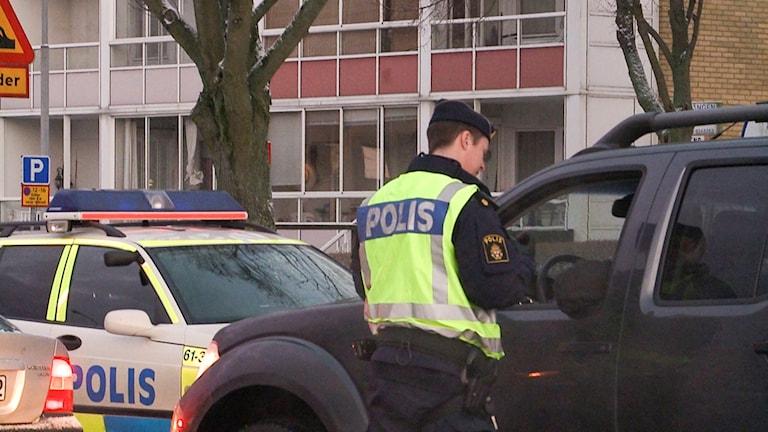 En polis har stannat en bil och samtalar med föraren
