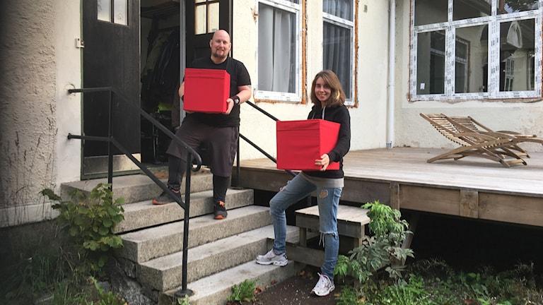 Två personer står och håller i en flyttlåda på en trappa utanför ett hus.