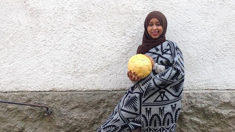 Illham Abdalla leder fotbollsskola för tjejer i Växjö. Håller i en fotboll.