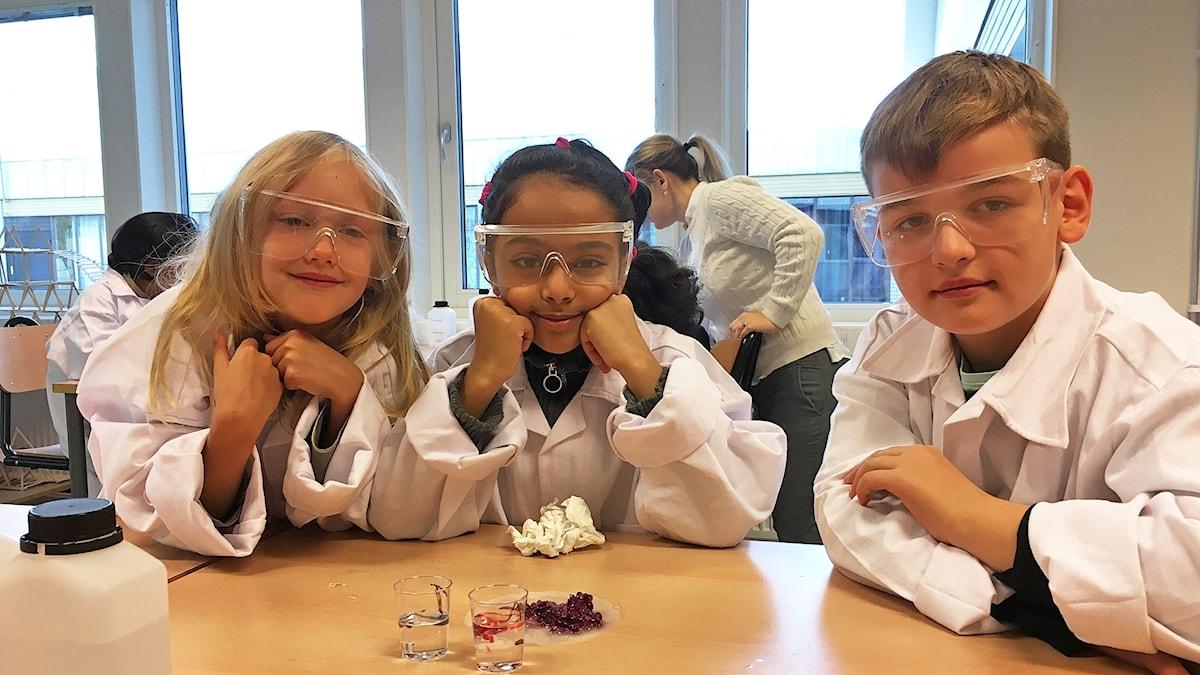 Tre elever i labbrockar