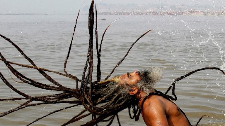 En indisk man med dreadlocks står i vattnet och kastar håret bakåt så det flyger åt alla håll tillsammans med massa vattendroppar.