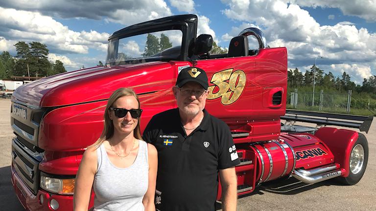 Två personer står framför en röd lastbilscabriolet