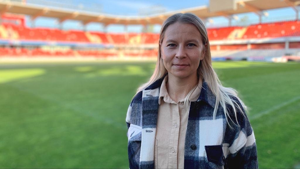 Kvinna framför fotbollsplan.