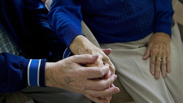 Äldre par som håller hand.