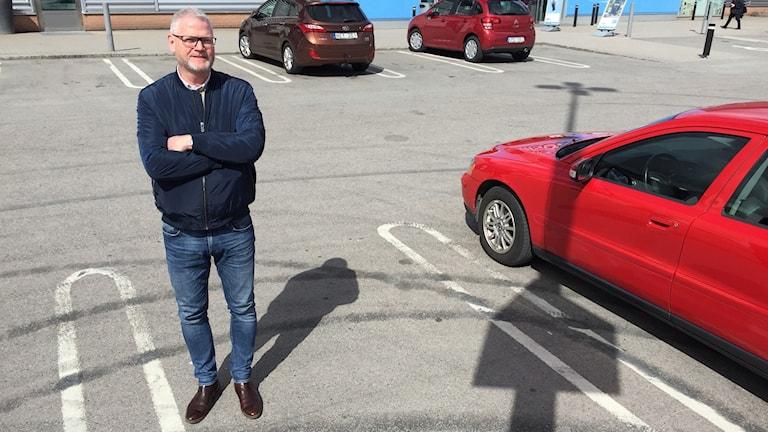 Mats Jäderberg står på parkeringen vid en röd bil och man ser sladdspår i asfalten.