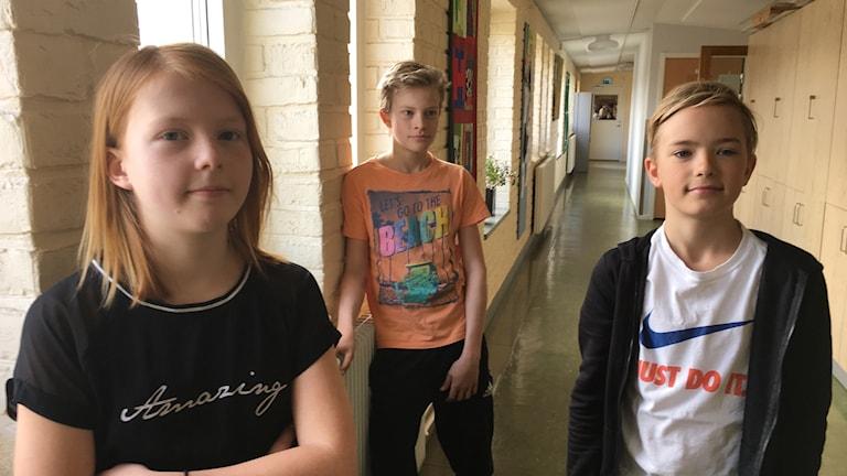I bild eleverna Lisa, Milo och Isak som går i femman i Växjö som alla har kontokort som de kan handla på. De står vid skolans två fönsterpelare.