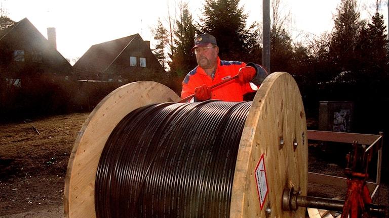 Dragning av bredbandskabel i Vendelsö. En man sysselsatt med monteringsarbete vid en kabelrulle.