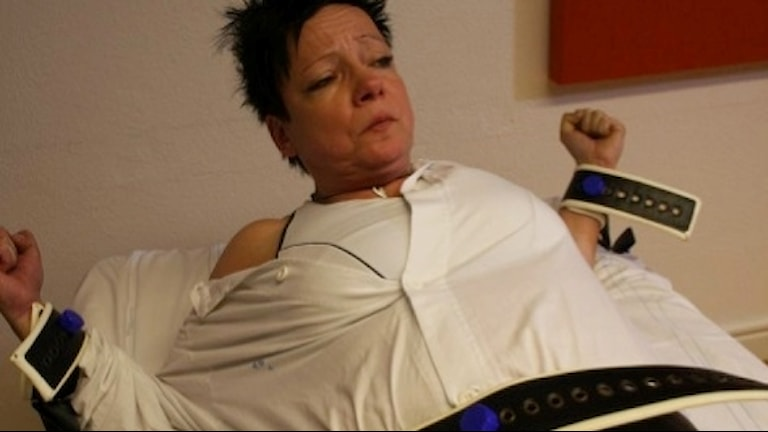 En kvinna ligger fastspänd efter en tvångsåtgärd inom den allmänna psykiatrin.