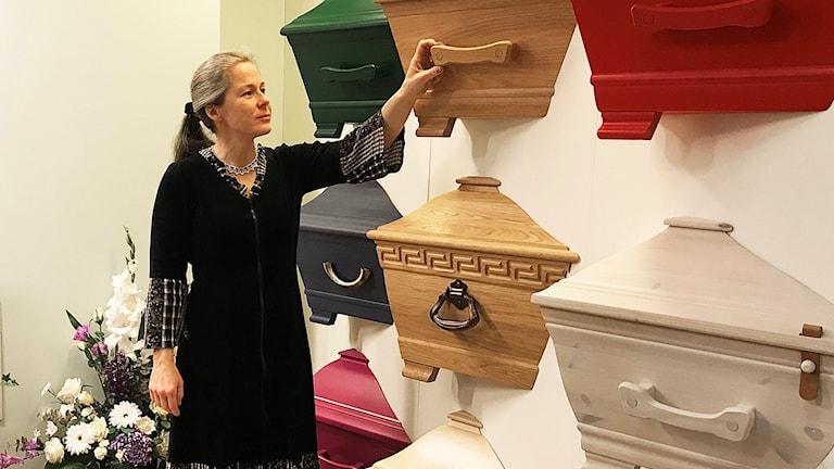 En kvinna står vid kistor.