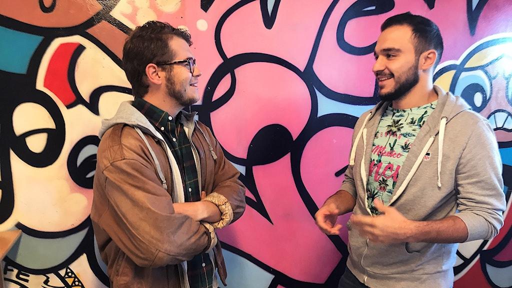 Två män står och pratar vid en graffitivägg.