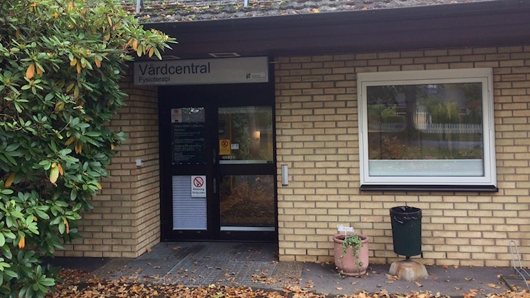 Ingången på Lenhovads vårdcentral. Bild tagen under höstmånader och ingången pryds av nedfallna löv. Vårdcentralen har en tegelfasad av en gulare nyans.