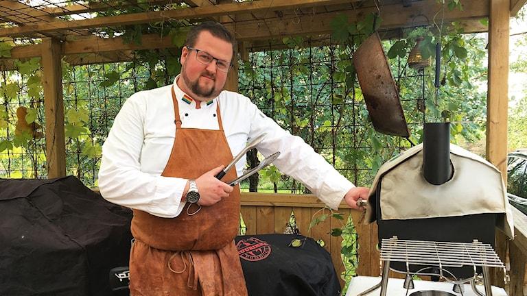 Kocken står vid sin grill.