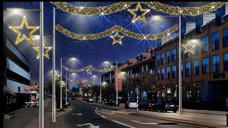 Animerad bild av Norra Esplanaden i Älmhult. Bilden föreställer kvällstid. Girlander med ljus hänger tvärs över gatan, mellan gatans lyktstolpar. I mitten av girlanderna sitter en stor guld stjärna även den med ljus. På utsidan av lyktstolparna finns samma  typ av guldstjärna med ljus placerad över gångbanan.