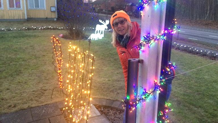 Ingela Strand tittar fram bakom en av husets pelare som är klädd med ljusslingor i olika färger. Bredvid en buske med massa gula ljus. Bakom en vit belyst älg och massa ljus i häcken runt huset.