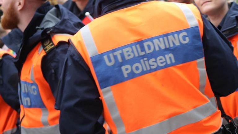 "En oreange väst som det står ""Utbildning polisen"" på."
