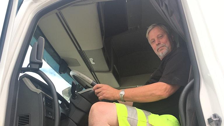 I lastbilen sitter Leif Karlsson i förarhytten på sin lastbil. Han har vänster hand på ratten och tittar mot kameran.