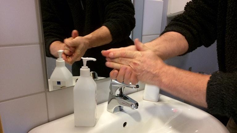 En som tvättar händerna med handsprit