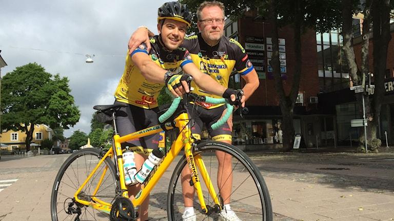 Eddy Proca och Thomas Forsstedt står beredda med cykelklädsel vid Eddys cykel.