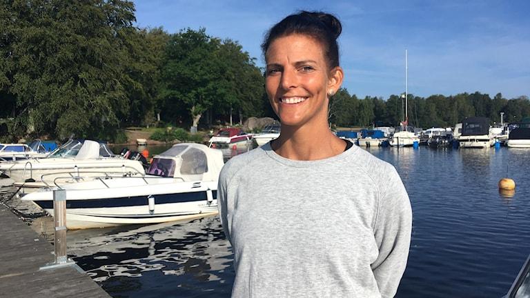 En tjej står vid båtar i en hamn