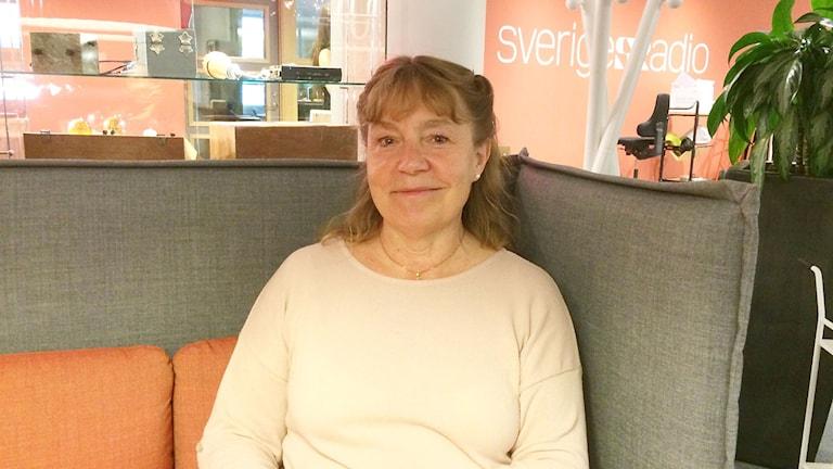 Kristiina Hallenberg-Persson sitter i en soffa.